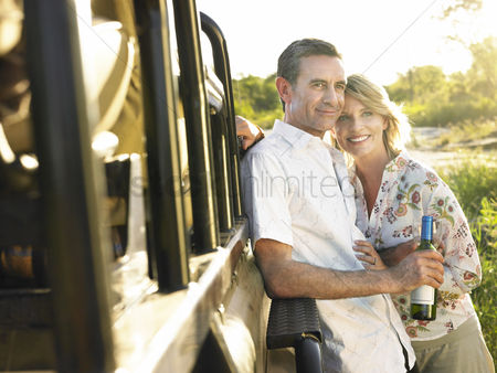 Wine bottle : Adult couple standing by jeep man holding bottle of wine smiling