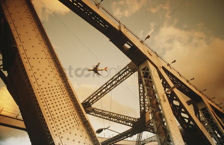 Transportation : Airbourne passenger jet viewed through bridge superstructure