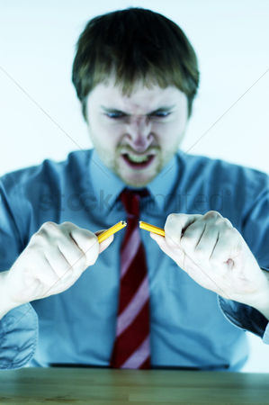 Blow up : An angry looking man in blue shirt and tie breaking a pencil into two