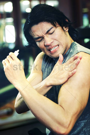 Pain : An asian guy applying muscle relief lotion on his arm