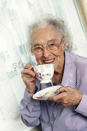 Bespectacled : An old bespectacled woman sitting on the couch drinking tea