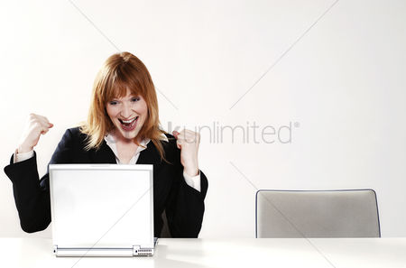 People : An overjoyed businesswoman after reading the good news on her laptop
