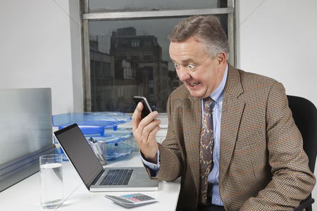 Office worker : Angry middle-aged businessman looking at cell phone in office