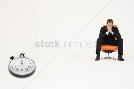 Loss : Anxious businessman sitting on chair with stopwatch showing time representing loss of time