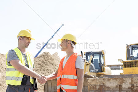 Supervisor : Architects shaking hands at construction site against clear sky