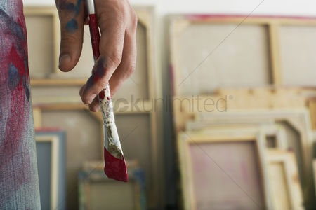 Contemplation : Artist holding paint brush standing in studio close up on hand