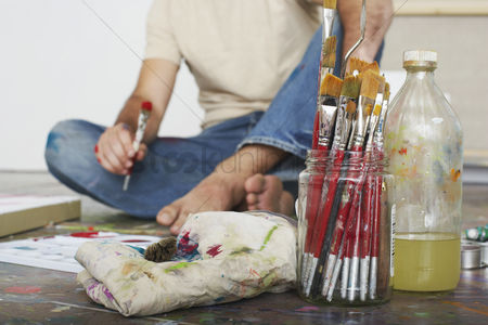 Denim : Artist sitting on floor focus on paint brushes and materials