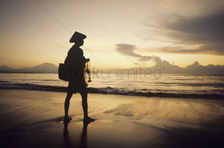 Traditional clothing : Asian fisherman on shore watching sunset