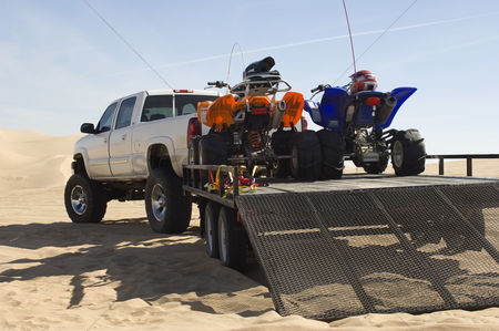 Truck : Atvs on trailer behind pickup truck