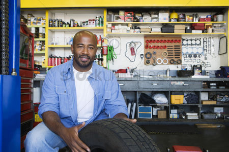 Posed : Auto mechanic working on a tire