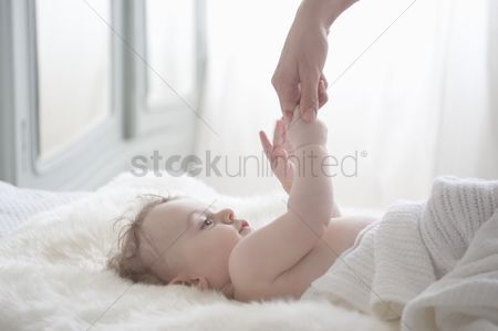 Interior : Baby boy reaches for mother s hand