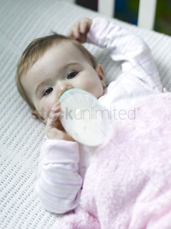 Appetite : Baby girl lying on the crib drinking milk
