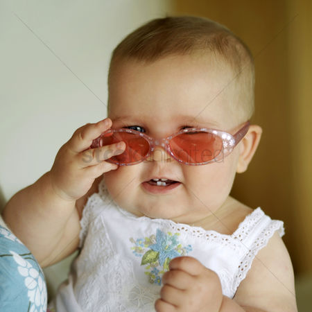 Adorable : Baby girl smiling while wearing sunglasses