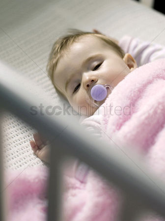 Pink : Baby girl with pacifier sleeping in the crib