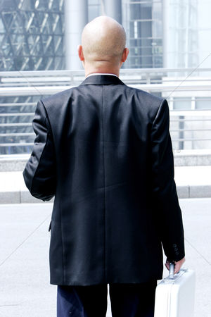 Bald : Back shot of a bald man in business suit carrying a suitcase