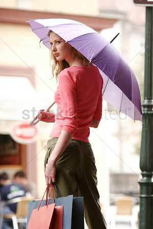 Outdoor : Back shot of a lady holding a purple umbrella and some paper bags