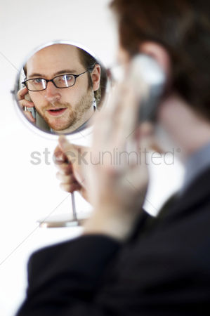 Determined : Back shot of a man looking at a mirror he is holding while talking on the hand phone