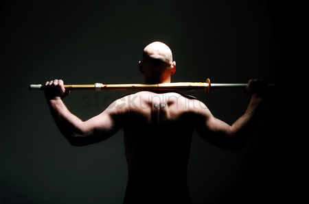 Strong : Back shot of shirtless man holding sword