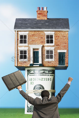 Celebrating : Back view of victorious businessman with briefcase in front of house on money rolls