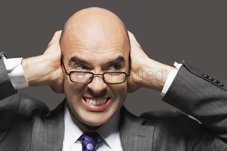 Bald : Bald businessman holding hand over ears looking sideways making a face