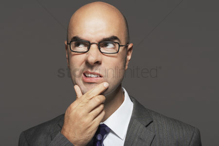 Loss : Bald businessman wearing glasses with hand on chin making funny face