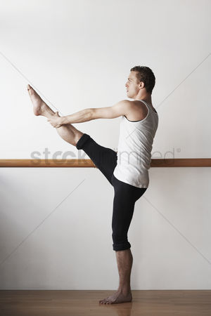Arm raised : Ballet dancer stretching at bar