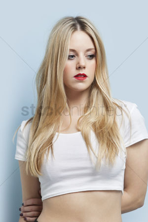 Pensive : Beautiful blond woman with red lips looking down against light blue background
