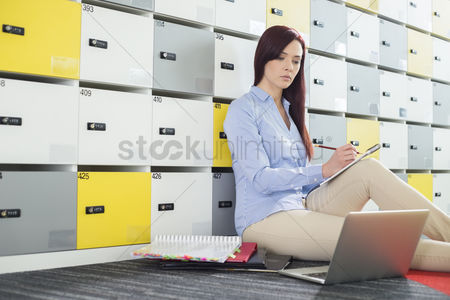 Notepad : Beautiful businesswoman using laptop while writing in locker room at creative office