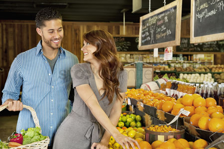 Supermarket : Beautiful young couple looking at each other while shopping in supermarket