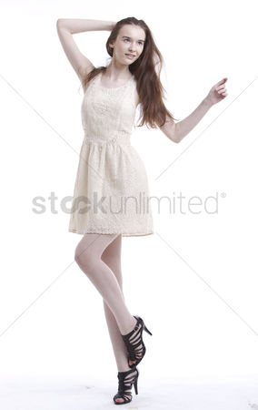 White hair : Beautiful young woman in dress with hand in her hair looking away against white background