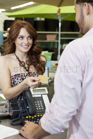 Supermarket : Beautiful young woman paying through credit card in store