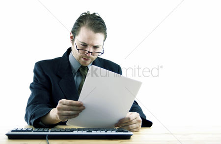 Bespectacled : Bespectacled businessman reading documents