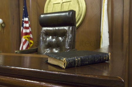 Flag : Bible beside judges chair in court