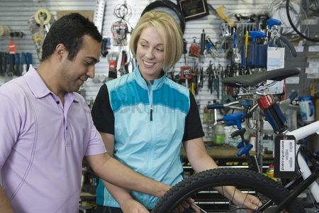 Fixing : Bike shop assistant helps female cyclist