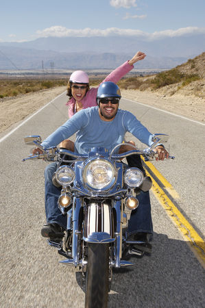 Arm raised : Bikers riding on desert road
