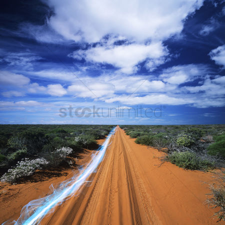 Transportation : Blue streak of light on dirt road against cloudy sky