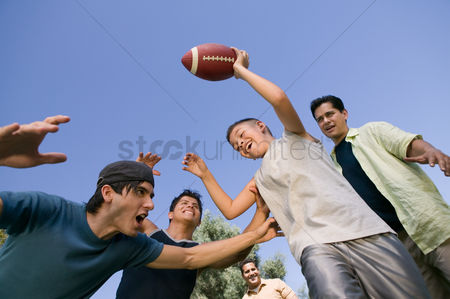 Arm raised : Boy  13-15  playing football with group of young men low angle view