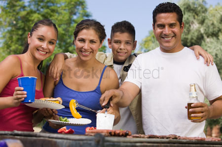 Daughter : Boy  13-15  with family at outdoor grill front view