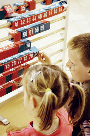 School : Boy and girl playing with a big abacus