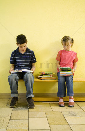 School : Boy and girl sitting on the bench with books on the lap