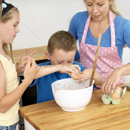 Egg tray : Boy breaking egg into mixing bowl  woman and girl watching