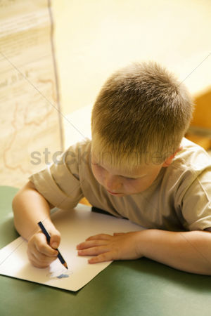 High school : Boy colouring in the classroom
