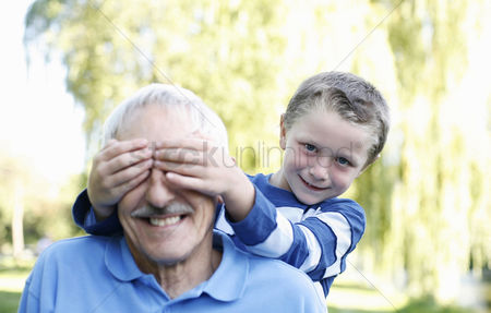 Two people : Boy covering his grandfather s eyes