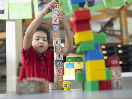 Toy : Boy playing with alphabet blocks in classroom