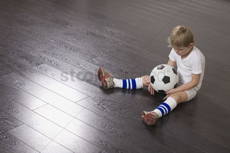 Loss : Boy sitting on floor holding soccer ball