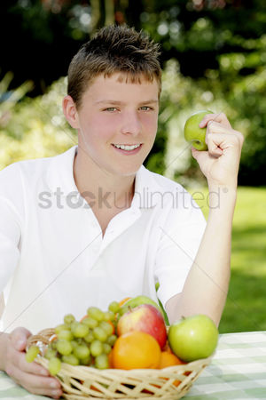 Green grapes : Boy smiling at the camera while holding a green apple