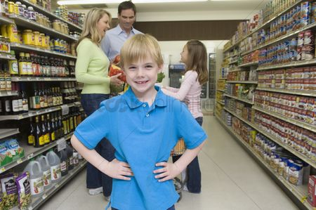 Shopping background : Boy stands with hands on hips with family shopping in supermarket