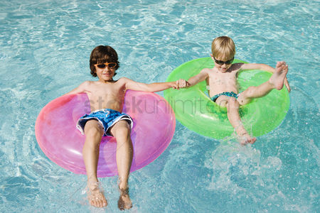 Young boy : Boys on float tubes in swimming pool