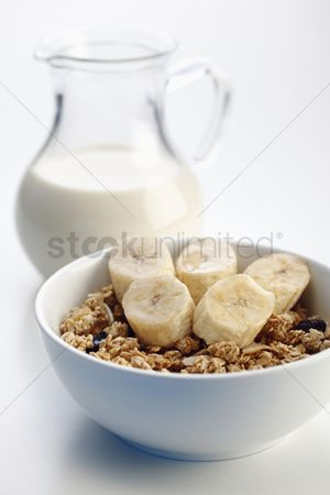 Two people : Breakfast of muesli with banana  milk and honey