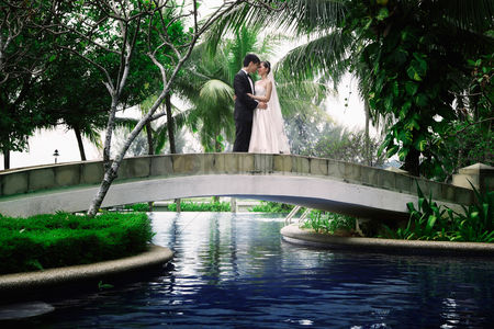 Asian : Bride and groom embracing on bridge over swimming pool